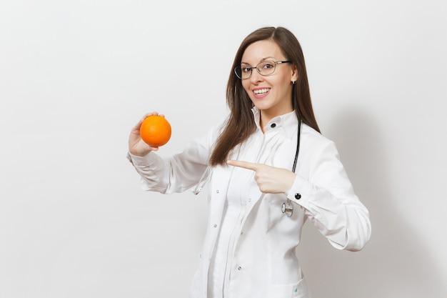 청진 기, 흰색 배경에 고립 된 안경 쾌활 한 자신감 꽤 젊은 의사 여자. 오렌지를 들고 의료 제복을 입은 여성 의사. 의료 인력, 건강, 의학 개념입니다.