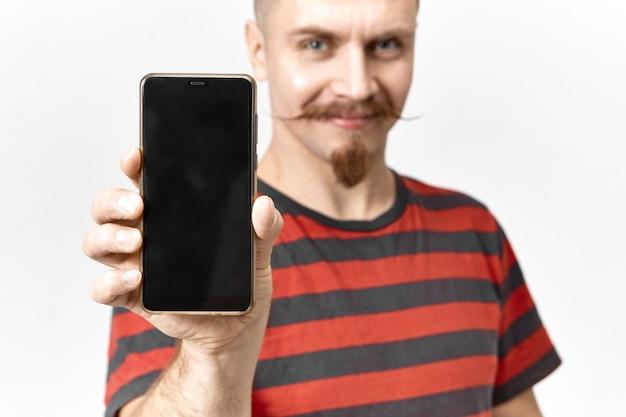 행복 하 게 웃 고, 완벽 한 디자인과 copyspace 디스플레이와 현대적인 브랜드의 새로운 검은 휴대 전화를 보여주는 쾌활 한 확신 젊은 파란색 된 남자. 전자 장치로 손에 선택적 초점