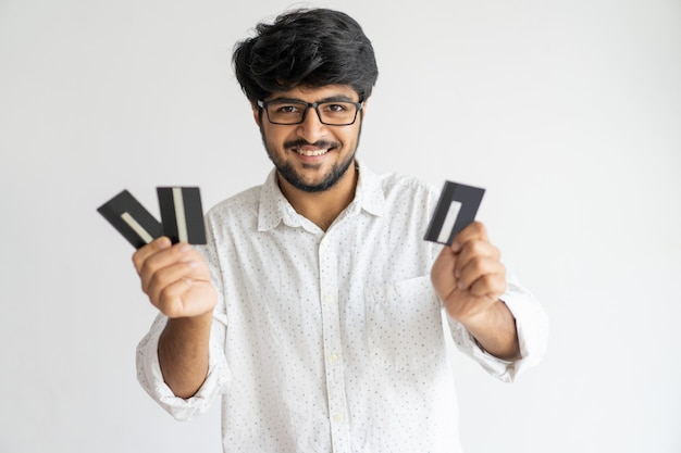 Cheerful confident young indian credit card holder enjoying his opportunities.