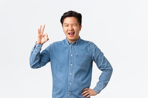 陽気な自信のあるアジア人男性は、すべてをコントロールし、ウィンクを励まし、大丈夫なジェスチャーを示し、計画を承認し、人を祝福し、よくやったと言って、素晴らしい仕事を評価し、白い背景に立っています。