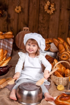 Cheerful cook baby laughing playing chef, bakery lot of bread
