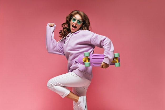 Cheerful cool girl in purple hoodie and white pants jumps on isolated