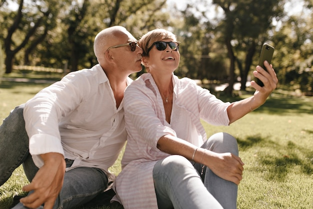 Cheerful cool woman with blonde hair in striped modern blouse and glasses sitting on grass, smiling and making selfie with grey haired man in park.