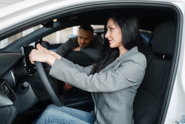 陽気なカップルがショールームで新しい車を買う、ホイールの後ろの女性。
