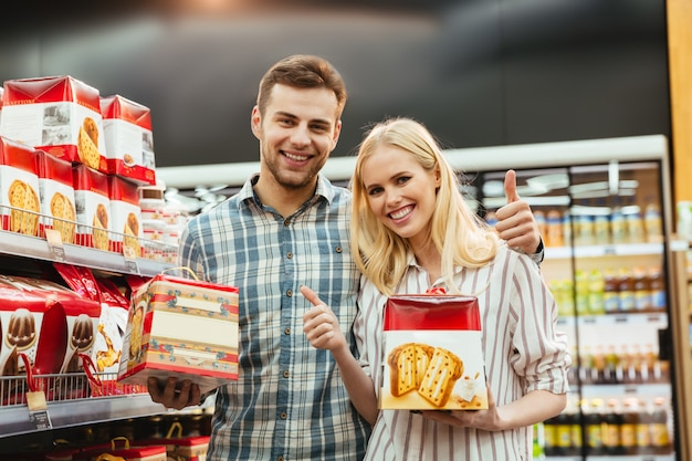 Cheerful couple buying panettone at supermarket