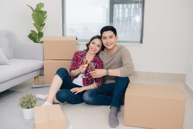 床に座ってシャンパンで彼らの新しい家を祝う陽気なカップル