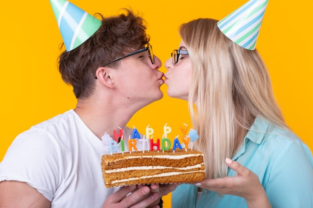 쾌활한 커플의 매력적인 남자와 종이 모자를 쓴 귀여운 소녀는 어리석은 얼굴을 하고 노란색 배경에 생일이 새겨진 케이크를 손에 들고 있습니다. 개념 인사말과 장난입니다.
