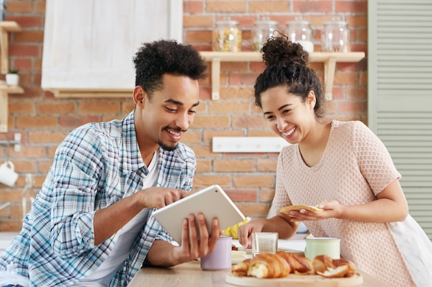 Cheerful couple choose new furniture in kitchen, look happily into screen of tablet