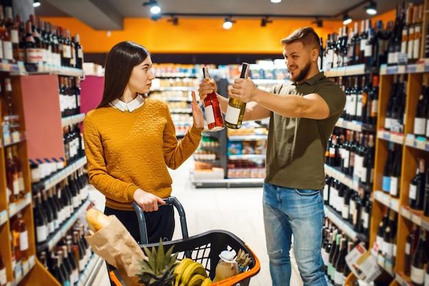 Веселая пара, выбирая алкоголь в супермаркете