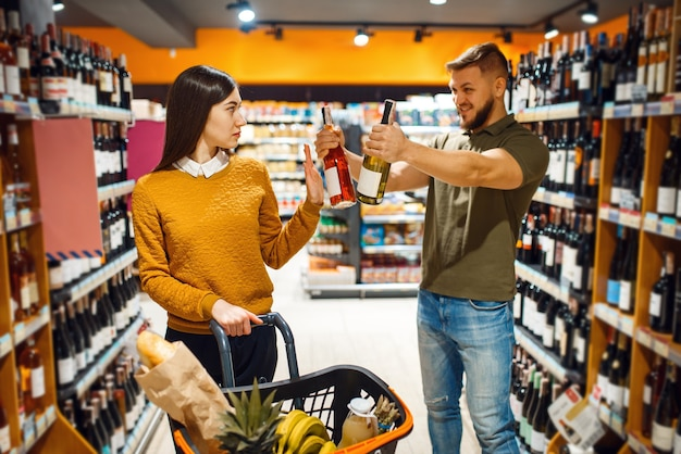 Cheerful couple choosing alcohol in supermarket