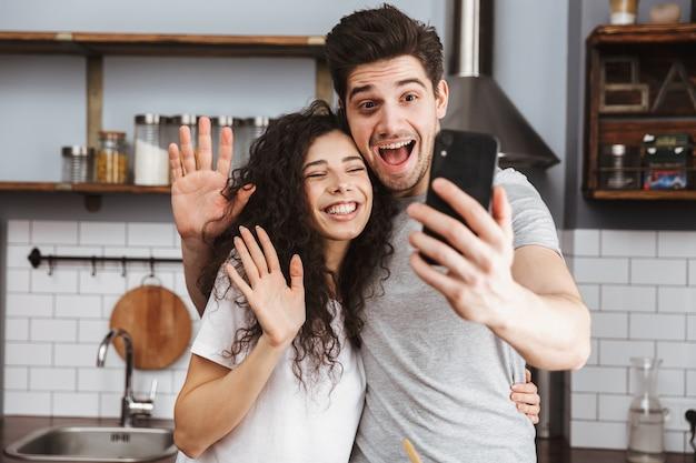 Веселая пара готовит на кухне, веселится, делает селфи