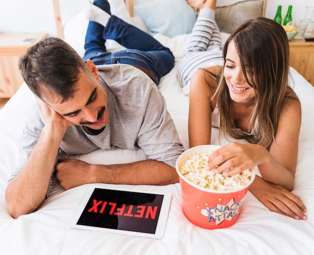 Веселые пары едят попкорн и смотрят шоу netflix