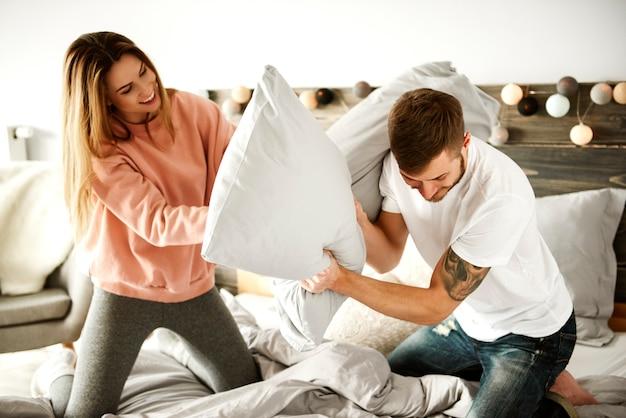 寝室で楽しんでいる陽気なカップル