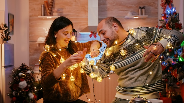 Cheerful couple getting tangled in string of twinkle lights