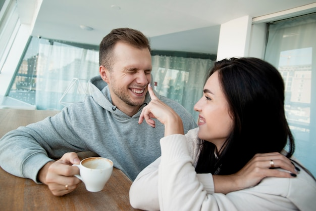 커피 한 잔과 함께 즐거운 시간을 보내는 쾌활한 커플. 행복한 검은 머리 여자가 남자의 코에 손가락을 대고 웃고 있습니다. 곁눈질 하 고 카푸치노 컵을 들고 남자입니다.