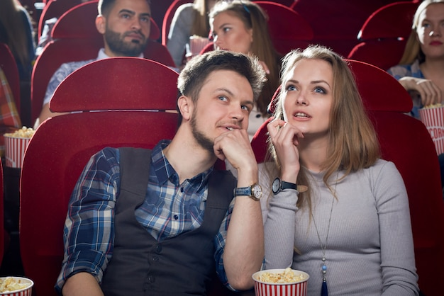 Cheerful couple having date in cinema.
