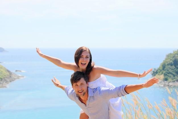 Веселая пара веселится в отпуске на берегу моря