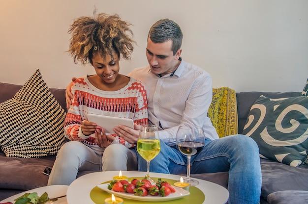 ソファーでタブレットを使って楽しいカップル。家庭での混合カップルタブレットとのショッピング。ミックスレースの女性。幸せなカップルは、タブレットコンピュータを使用してソファに座って