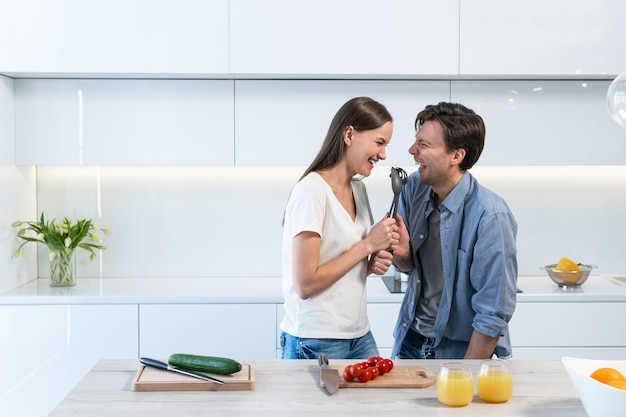 Cheerful couple having fun while cooking in the kitchen