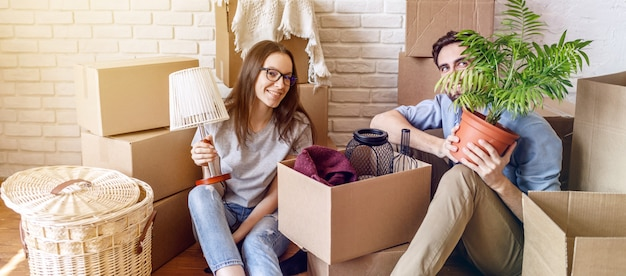 Cheerful couple having fun with boxes unpacking