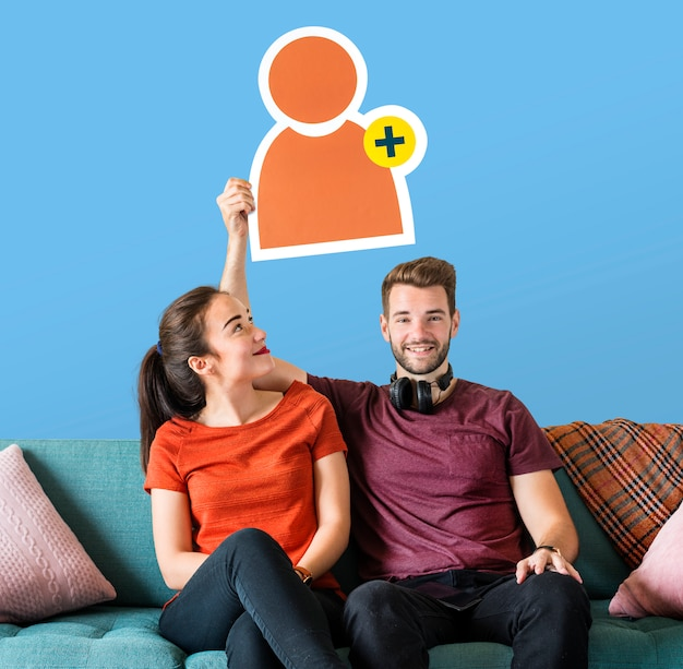 Cheerful couple holding a friend request icon