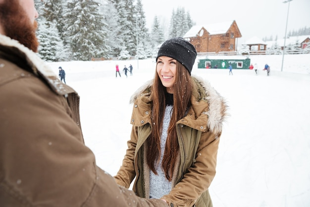 Cheerful couple holding hands and looking at eah other outdoors with snow on background