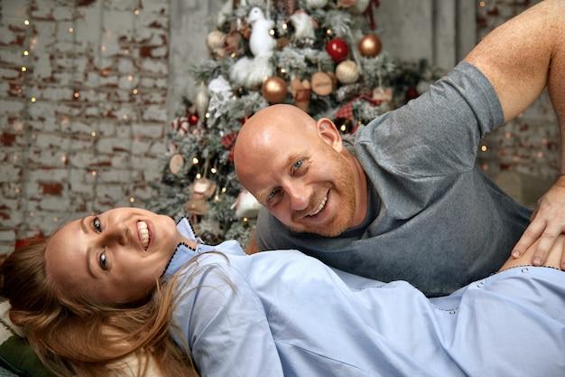 陽気なカップルを抱いて、クリスマスイブに一緒に楽しんでいます。奇跡、家族の結婚、新年の若いカップルを見越してクリスマスコンセプト。