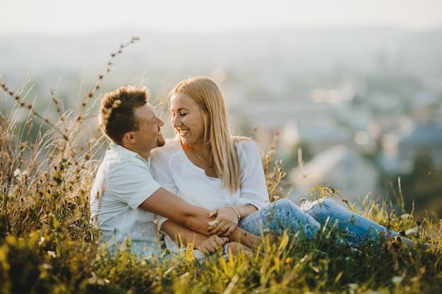 Le coppie allegre si abbracciano tenero che si siede sul prato inglese verde nel bello giorno di estate