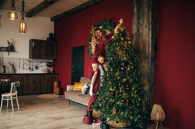 Веселая влюбленная пара в одной пижаме вместе украшает елку дома