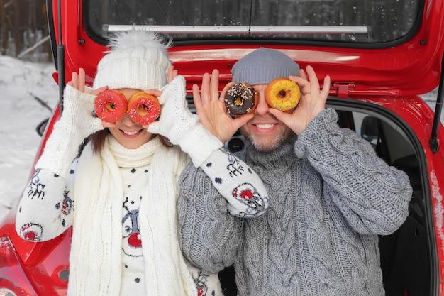 冬の森の車のトランクに座っているドーナツに恋する陽気なカップル。