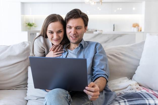 집에서 노트북 화면을 보고 있는 쾌활한 커플