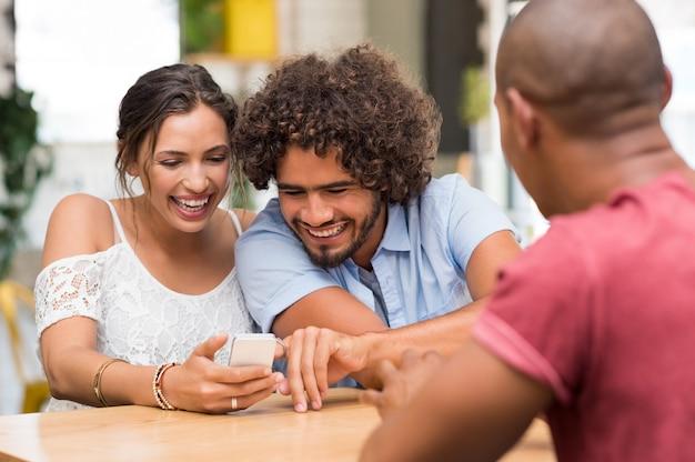 スマートフォンを見て笑っている陽気なカップル