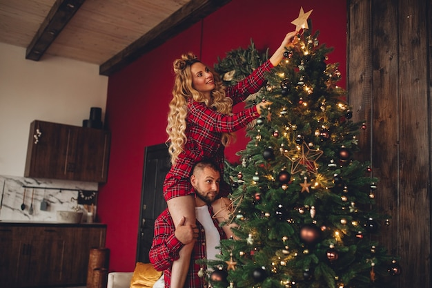 Cheerful couple in love in the same sleepwear decorates christmas tree together at home