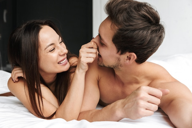 Cheerful couple man and woman hugging together, while lying in bed at home or hotel apartment
