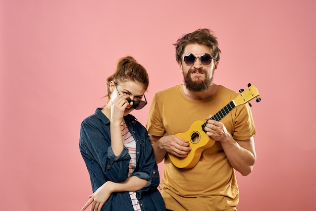 Cheerful couple man and woman with ukulele, lifestyle on a pink background