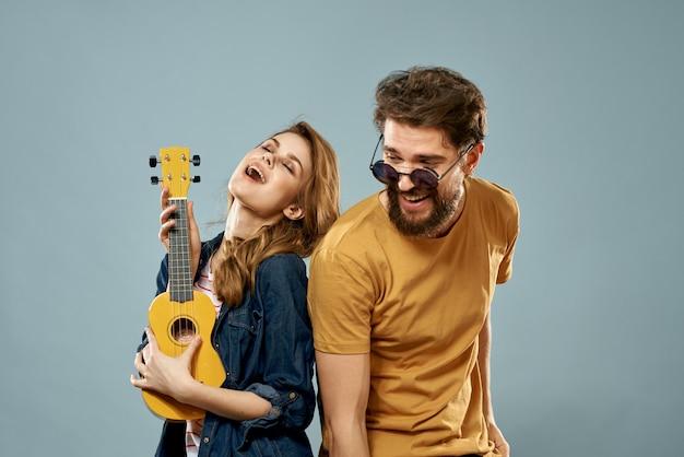 Cheerful couple man and woman with ukulele, lifestyle