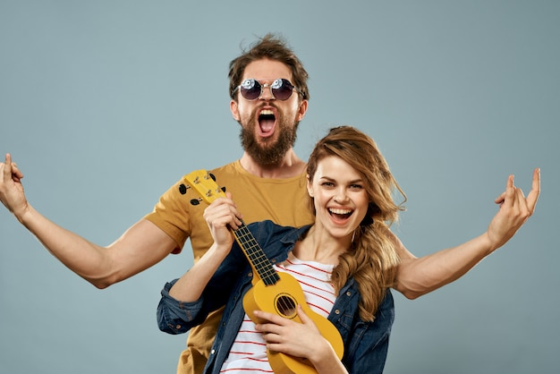 Cheerful couple man and woman with ukulele