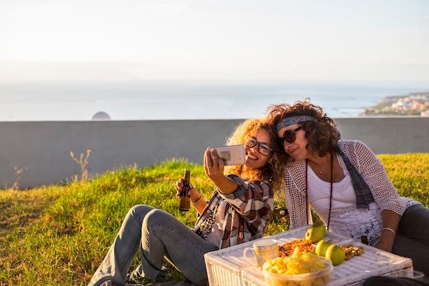 屋外でピクニックを楽しみ、自撮り写真を撮る中高年の陽気なカップル