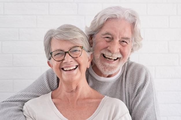 서로 껴안고 있는 두 명의 아름다운 노인 - 집에서 즐거운 시간을 보내고 있는 쾌활한 커플 - 고요한 은퇴 개념