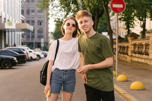 Веселая пара молодых людей и девушка гуляют по улице в теплый летний день