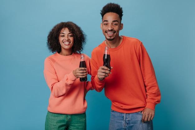 Cheerful couple in orange sweatshirts holding soda water