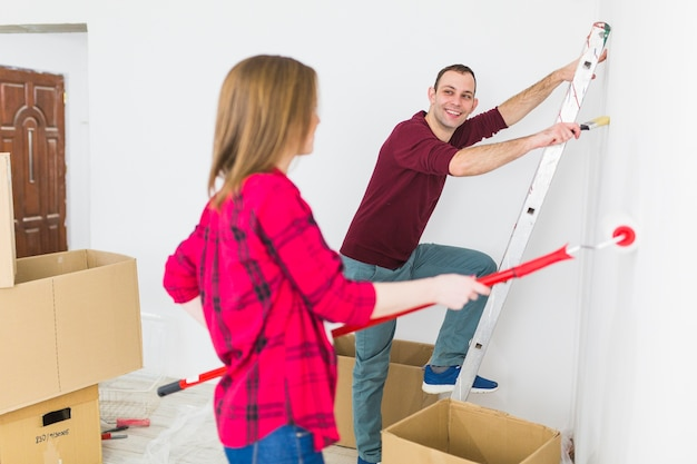 Cheerful couple painting walls in apartment