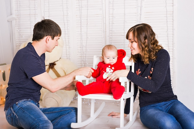 Cheerful couple playing with baby boy at home.