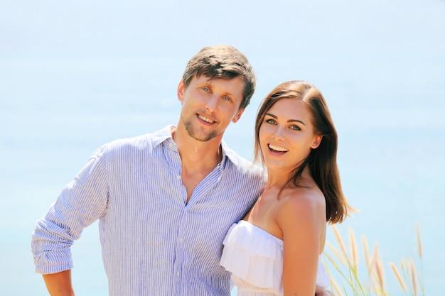 Веселая пара портрет позирует на синем море
