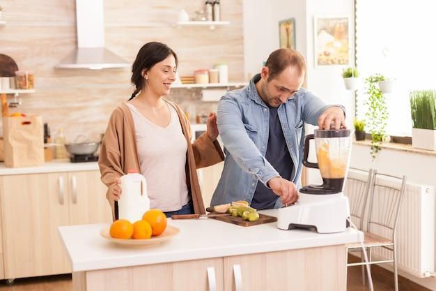 쾌활한 부부는 믹서기를 사용하여 스무디를 준비합니다. 부엌에서 우유병을 들고 있는 아내. 건강하고 평온하고 쾌활한 생활 방식, 다이어트를 먹고 포근하고 화창한 아침에 아침 식사를 준비합니다.