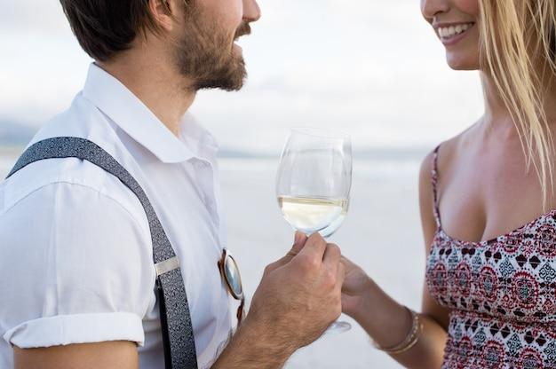 ビーチで乾杯を上げる陽気なカップル