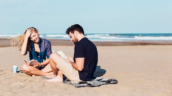 Cheerful couple reading books on beach