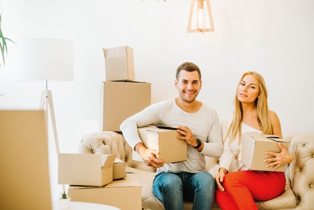 Cheerful couple relocating in apartment