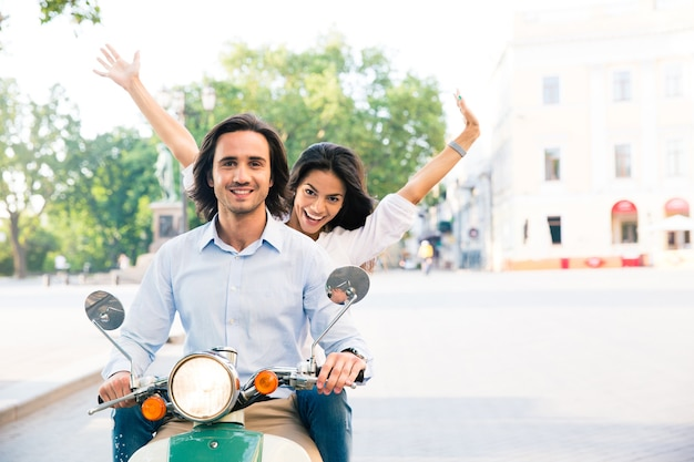 Cheerful couple riding on a scooter