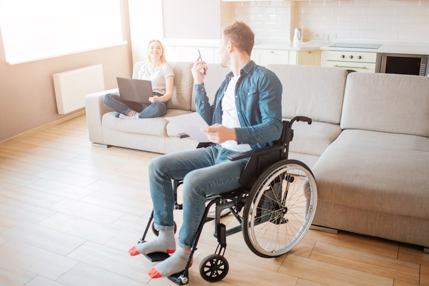 Cheerful couple in room together. young man with inclusiveness sit on wheelchair and look back on woman.